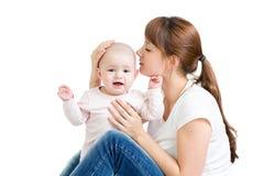Den lyckliga modern som kysser henne som är nätt, behandla som ett barn flickan Royaltyfria Bilder