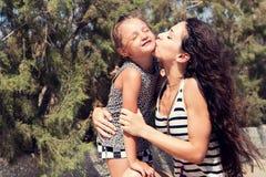 Den lyckliga modern som kysser hennes roliga tyckande om dotter på sommar, geen lodisar Royaltyfri Fotografi