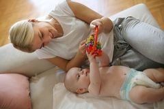 Den lyckliga modern som plying med hennes litet, behandla som ett barn pojken hemma arkivbilder