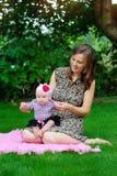 Den lyckliga modern som rymmer behandla som ett barn lite, flickan Royaltyfria Foton
