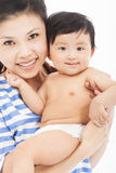 Den lyckliga modern som rymmer det förtjusande barnet, behandla som ett barn pojken Arkivfoton