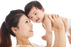 Den lyckliga modern som rymmer det förtjusande barnet, behandla som ett barn pojken Arkivbild