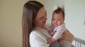 Den lyckliga modern som rymmer ett nyfött, behandla som ett barn i hennes armar stock video