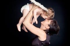 Den lyckliga modern som rymmer henne, behandla som ett barn dottern med ängelvingar Royaltyfri Fotografi