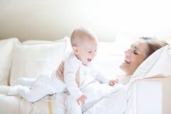 Den lyckliga modern som rymmer hennes älskvärda le, behandla som ett barn Arkivbild