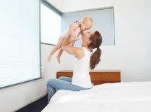 Den lyckliga modern som spelar med, behandla som ett barn i sovrum Arkivfoton
