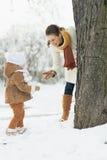 Den lyckliga modern som spelar med, behandla som ett barn i vinter utomhus Fotografering för Bildbyråer