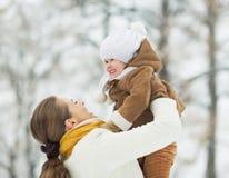 Den lyckliga modern som spelar med, behandla som ett barn i vinter utomhus Royaltyfri Foto