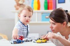 Den lyckliga modern som spelar med, behandla som ett barn pojken hemma Arkivfoto