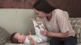 Den lyckliga modern som spelar med lite, behandla som ett barn på soffan stock video