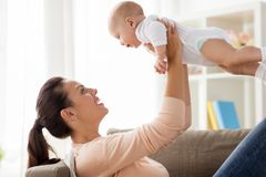 Den lyckliga modern som spelar med lite, behandla som ett barn pojken hemma royaltyfria bilder