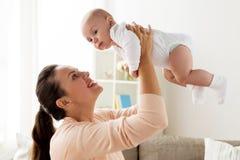 Den lyckliga modern som spelar med lite, behandla som ett barn pojken hemma royaltyfria foton