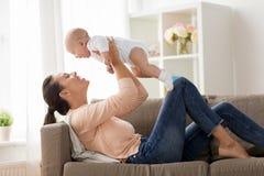 Den lyckliga modern som spelar med lite, behandla som ett barn pojken hemma fotografering för bildbyråer