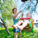 Den lyckliga modern som vaggar skratta, behandla som ett barn på en gunga Fotografering för Bildbyråer