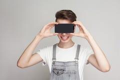 Den lyckliga moderna unga pojken i deminoveraller och den vita T-tröja står royaltyfria foton