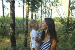 Den lyckliga moderns mamman och sonen i en pinjeskogmamma och sonen för dag ler och kramar Ferier och umgås för familj arkivbilder