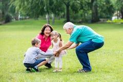 Den lyckliga morföräldern och barnbarn parkerar in arkivbilder