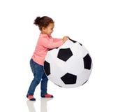 Den lyckliga mulatten behandla som ett barn lite flickan som spelar med bollen Royaltyfri Fotografi