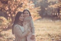 Den lyckliga mumen och dottern play höstparken Arkivbilder
