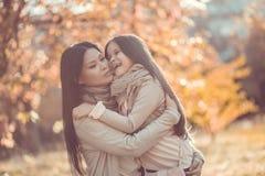 Den lyckliga mumen och dottern play höstparken Fotografering för Bildbyråer
