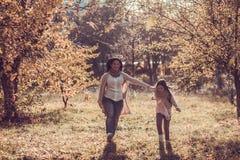 Den lyckliga mumen och dottern play höstparken Arkivfoton