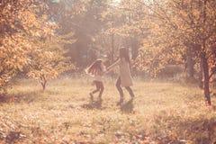 Den lyckliga mumen och dottern play höstparken Royaltyfri Fotografi