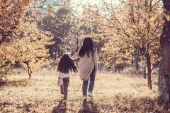 Den lyckliga mumen och dottern play höstparken Royaltyfri Bild