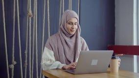 Den lyckliga muslim kvinnan pratar direktanslutet vid bärbara datorn i kafé med fri wifi lager videofilmer