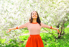 Den lyckliga nätta le unga kvinnan som tycker om lukten, blommar arkivbilder