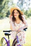 Den lyckliga nätta unga flickan som cyklar på sommar, parkerar Lyckligt koppla av tid i stad Härlig kvinna, solig dag arkivfoton