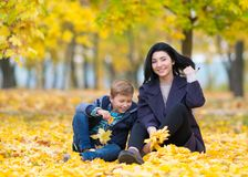 Den lyckliga nöjda modern och sonen som spelar i, parkerar arkivfoto