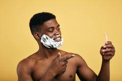 Den lyckliga nacked mannen har valt desposable rakknivar kassettrakkniv f?r sexiga grabbar arkivfoto