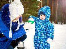 Den lyckliga och glade modern och barnet går på, lek i vinterskogpinjeskogen av den Chelyabinsk regionen, Ural, Ryssland Arkivfoto