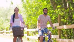 Den lyckliga parridningen cyklar på sommar parkerar arkivfilmer