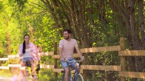 Den lyckliga parridningen cyklar på sommar parkerar lager videofilmer