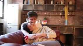 Den lyckliga parskämtandet för könsbestämmer på en soffa i vardagsrummet hemma stock video