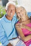 Den lyckliga pensionären kopplar ihop att le utanför i solsken Arkivfoton