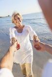 Den lyckliga pensionären kopplar ihop dansinnehav räcker på en tropisk strand Arkivfoton