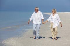 Den lyckliga pensionären kopplar ihop det gå innehav räcker den tropiska stranden Arkivbild