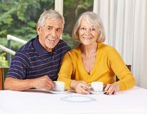 Den lyckliga pensionären kopplar ihop dricka kaffe Royaltyfri Foto