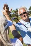 Den lyckliga pensionären kopplar ihop leka Golf arkivfoton