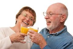 Den lyckliga pensionären kopplar ihop med exponeringsglas av orange fruktsaft Royaltyfria Bilder