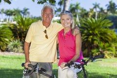 Den lyckliga pensionären kopplar ihop på cyklar parkerar in Royaltyfria Foton