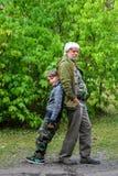 Den lyckliga pensionären och pojken i gräsplan parkerar royaltyfri foto