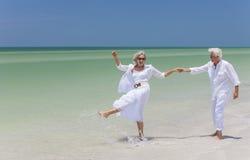 Den lyckliga pensionären kopplar ihop dansinnehav räcker på en tropisk strand Royaltyfri Foto