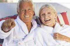 Den lyckliga pensionären kopplar ihop i badrockar på den vård- Span Fotografering för Bildbyråer