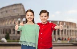 Den lyckliga pojke- och flickavisningen tummar upp över coliseum Royaltyfria Bilder