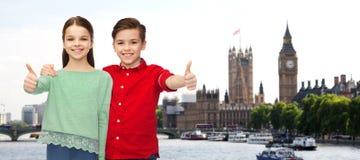 Den lyckliga pojke- och flickavisningen tummar upp över london Royaltyfria Foton
