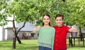 Den lyckliga pojke- och flickavisningen tummar upp över trädgård Arkivbild