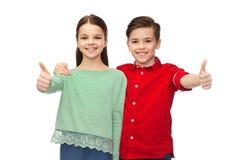 Den lyckliga pojke- och flickavisningen tummar upp Arkivfoton